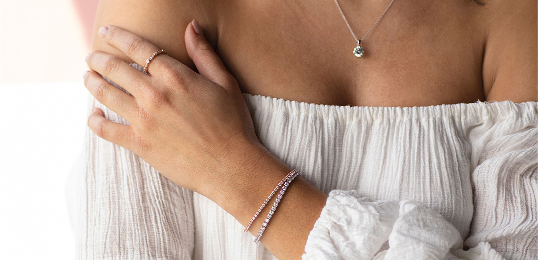 Model is shown wearing one lab grown diamond pendant, an accented wedding band and two bracelets