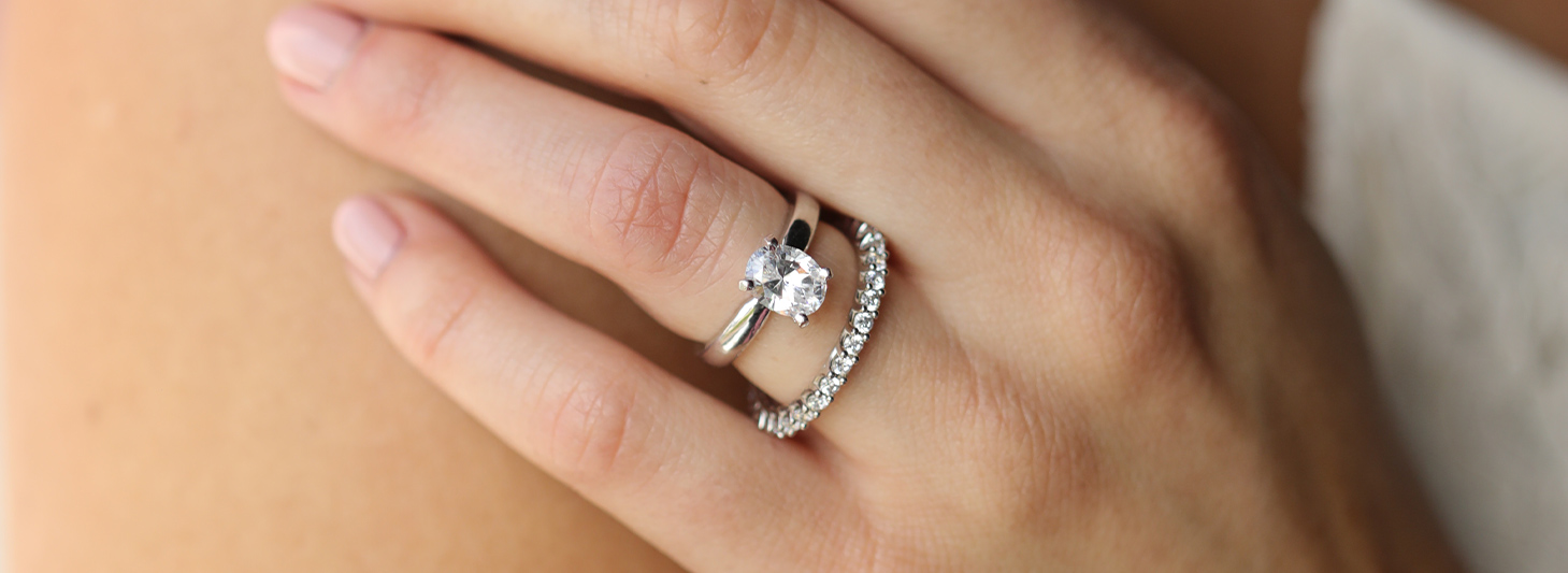 An oval cut stone paired with an accented wedding band